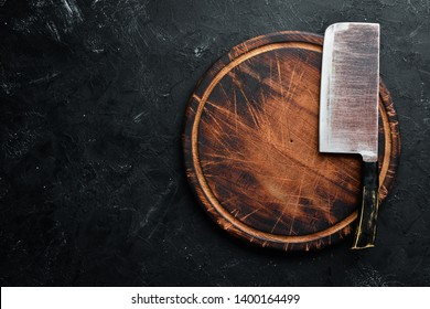 The old kitchen knife and Wooden boards on a black background. Top view. Free space for your text.