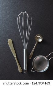 Old knife, whisk, spoon and sieve presented on a black concrete background with space for text. Top view