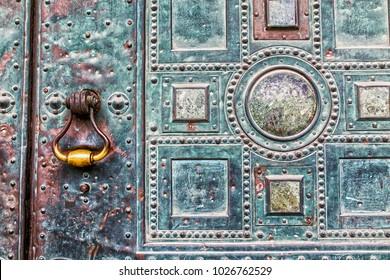 old knocker at a metal door