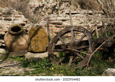 an old Kvevri laying next to the dilapidated wooden wheel of a disused cart with brick background, narikala fortrees in tbilisi, georgia