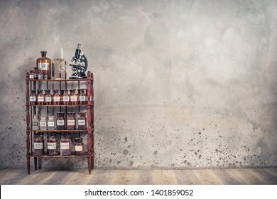 Old laboratory bottles, antique microscope, vintage lab glassware support on the wooden shelving front concrete wall background. Retro style filtered photo