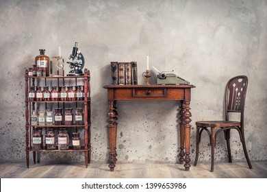 Old laboratory bottles, vintage microscope, glassware support on the shelving, classic typewriter and antique books on wooden table and chair front concrete wall background. Retro style filtered photo
