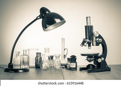 Old laboratory glass, retro microscope and desk lamp. Vintage style sepia photo