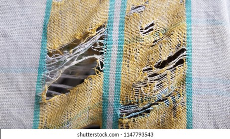 Old lacerated towel with worn textile structure closeup. Discolored striped torn rags background with holes in fabric.