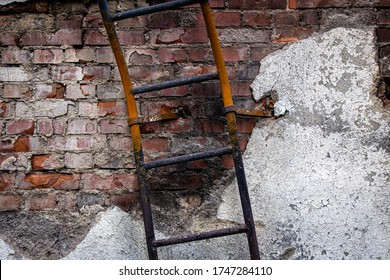 An old ladder in front of a wall