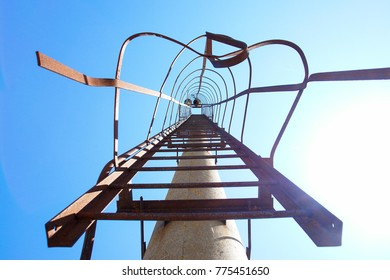 An old ladder stairs leading us to the shiny blue skies. Stairs to heaven. Metal ladder covered with rust and located on a pillar.
