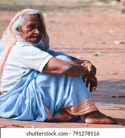 Old lady across the street sitting (Color) (City - Jabalpur, Country - India, Date - 1.11.2017. An old lady sitting across the street and looking at the subject)