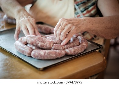 Old lady arranging home made sausages in spiral formation on metal tray, working on table.