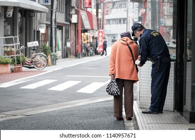 An old lady is asking direction and assistance from a local police on the street of japan. The policeman is wearing his uniform showing 'Policeman' on the back.