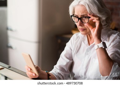 Old lady is being worried receiving new message on her phone