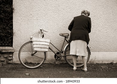 Old lady with bicycle in Argentat market , Correze, France