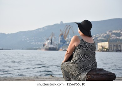 Old lady chilling on the Molo Audace in Trieste, Italy. In the background the Porto Veccio (Old harbour) can be seen.