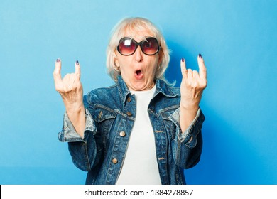 An old lady in a denim jacket, sunglasses makes a gesture on the rock on a blue background. Concept fashionable grandmother, old woman, action rockers Goat.