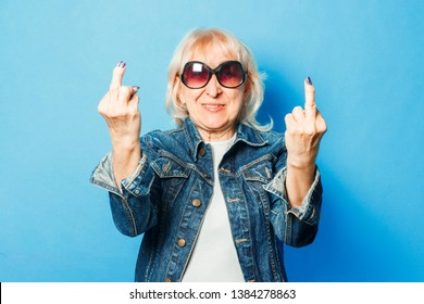 An old lady in a denim jacket, sunglasses makes an unpretentious gesture with the middle finger on a blue background. Concept fashionable grandma, old woman.