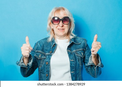 An old lady in a denim jacket and sunglasses is showing a gesture with her hands. Thumb up on a blue background. Concept fashionable grandma, old woman, funky action.