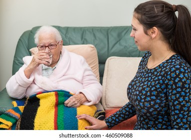 Old lady drinking glass of water to swallow tablets. Young lady smiling, pleased that old lady took medicine. Old lady looking off into distance on left.