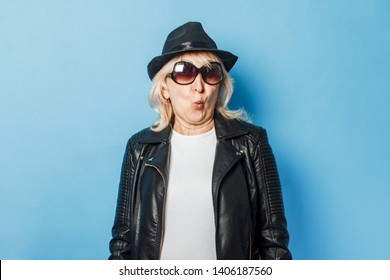 Old lady in glasses, leather jacket and hat on a blue background. Concept old rocker, grandmother in the heat, cool old woman