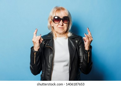 Old lady with glasses and a leather jacket is showing a gesture with her hands against a blue background. Concept old rocker, grandmother in the heat, cool old woman