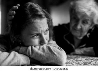Old lady grandma comforting a crying little girl granddaughter. Black and white photo.