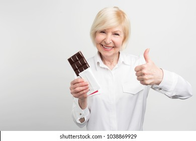 Old lady is holding a bar of good chocolate and looking straight ahead. She liked the taste of it. She could recommend this chocolate as the best one. Isolated on white background.