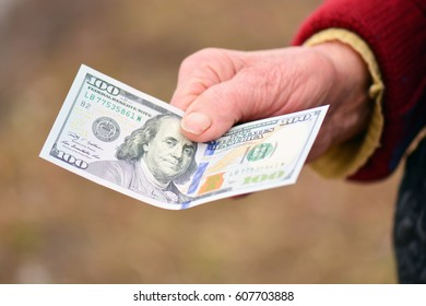 The old lady is holding money in her hand