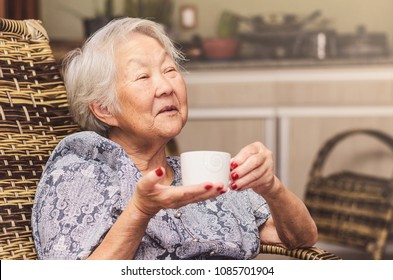 Old lady (japanese descendant) seated comfortably at home holding a cup of tea with a happy expression of who is having a good conversation or telling stories.