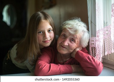 Old lady posing for a portrait with little girl great-granddaughter.