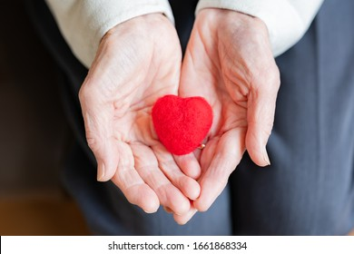 Old lady with red heart (happiness image)