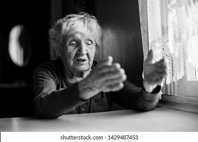 The old lady is sitting talking gesticulating at the kitchen table. Black and white photo.