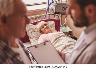 Old lady is sleeping in bed in the hospital ward while her husband and doctor are talking