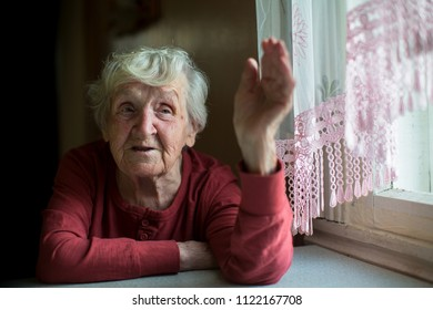 The old lady is talking sitting by the window.