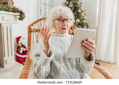 Old lady is using modern gadget in holiday