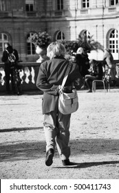 Old lady walking in Luxembourg garden. Back view. Urban scene. Paris (France) Selective focus on hands. Black and white.