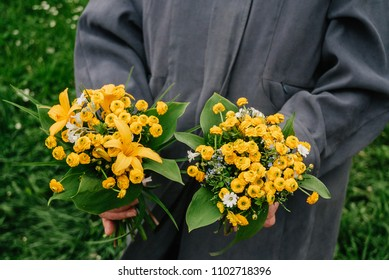 Old lady wearing gray coat selling handmade wild flowers on market hands close up
