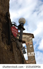 an old lamp and town arm on an ancient wall in foreground and the bell tower of a church in blurred background  in the village of Montalcino in Tuscany Italy vertical orientation