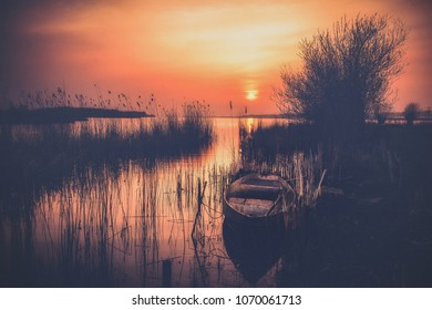 Old landscape with vintage rowing boat in a reed collar with atmospheric, intense sunset. Old pollard willows and drawn cloudy skies with sunbeams scorch the Dutch landscape with views over the lake.
