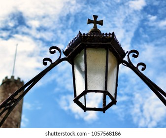 Old lantern with a Christian cross on a bright day
