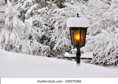 old lantern covered by snow in a garden