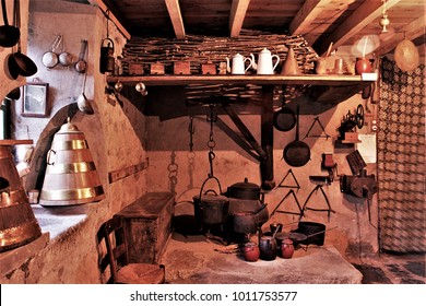 old lareira in Galicia, old country kitchen with hanging pans,old wooden cupboard in the kitchen of a rural house in Galicia, old wooden furniture,  typical rural cuisine of Galicia,