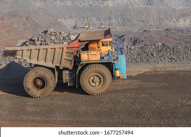 An old large mining truck loaded with iron ore in a quarry