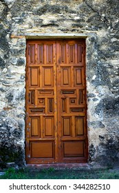 Old, large, ornate wooden doors standing against an old masonry wall  / Ornate Wooden Mission Doors / An interesting view of an old, large, ornate wooden doors standing against an worn masonry wall