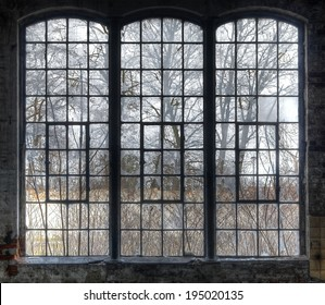 Old large window with broken panes in a deserted hall