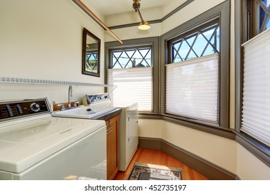Old laundry room interior with white appliances and vintage windows with gray trim.