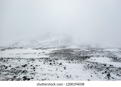 Old lava field in snow. Top of Askja volcano. September in Iceland. Trail to Viti lake.
