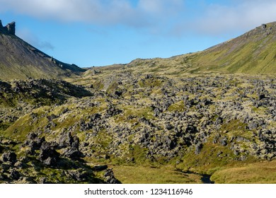 Old lava stream down a mountainside in Iceland covered with green grass.  Bright summer sunshine and blue sky