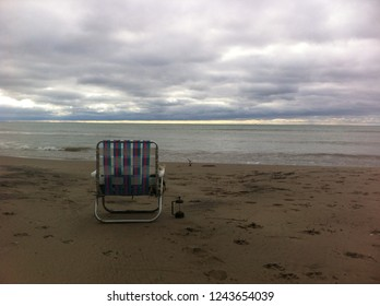 old lawnchair sitting empty on beach facing water, with cloudy sky and light on the horizon