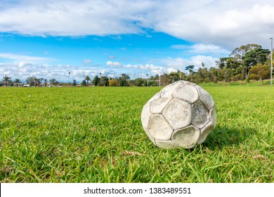 Old leak football/soccer ball abandoned on green grass field. Concept of sadness, hopeless and loneliness.