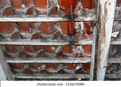 Old leaking roof tiles. Old timber roof support. Rotten wood on old loft. Water from the broken roof flowing into the old house.