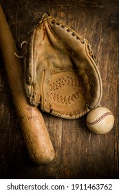 Old leather baseball glove lying on an antique table with ball and bat