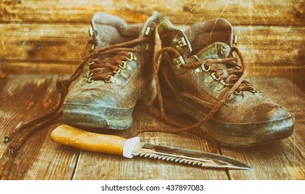 Old leather boots and hunting knife. Boots on a wooden background. Vintage toning